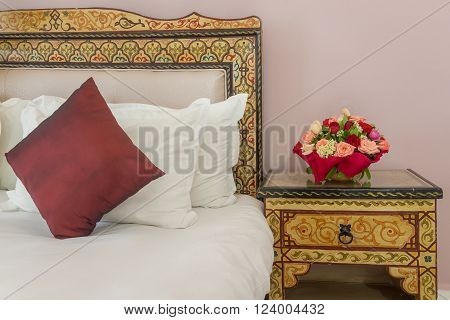 A bouquet of flowers on a bedside table next to a bed with a painted headboard