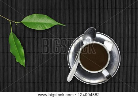 Coffee cup on black wood with spoon sugar and plants