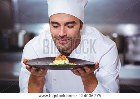 Male chef with eyes closed smelling food in commercial kitchen
