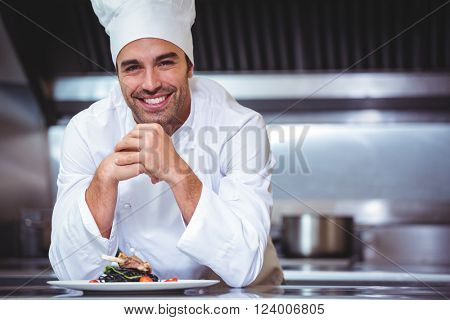 Chef leaning on the counter with a dish in a commercial kitchen