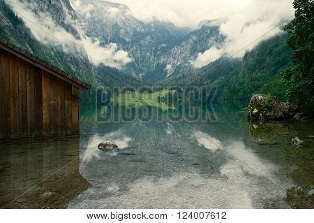Beautiful foggy view on the lake Königsee with a big stone in the foreground Germany