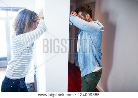 Couple leaning on opposite sides of the wall and feeling sad