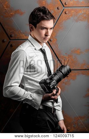 Professional photographer in a white shirt is posing in studio