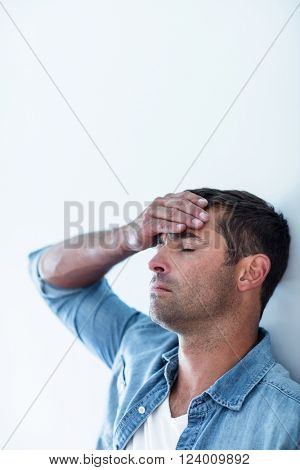 Close-up of upset man leaning on wall with hand on forehead