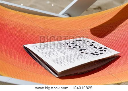 A crosswords game book on a deckchair