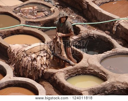 Fez, Morocco - May 31, 2013: People are in vats of different colored dyes and stained their skin. Leather dyeing and tannery Shuar, on which there is a dressing and a skin preparation for subsequent fabrication. They are located in the heart of the medina