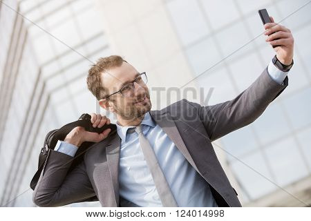 Happy businessman with a bag over his shoulder taking selfie outdoors ** Note: Soft Focus at 100%, best at smaller sizes