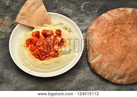 Top view of a bowl of edamame Hummus and pita bread. Horizontal format.