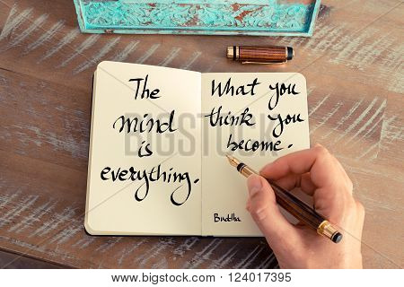 Retro effect and toned image of a woman hand writing on a notebook. Handwritten quote The mind is everything. What you think you become. - Buddha as inspirational concept image