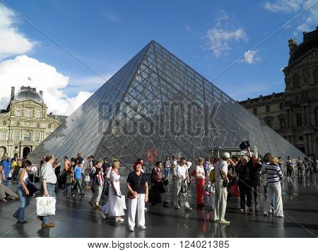 PARIS FRANCE - CIRCA AUGUST 2011: Tourists near the Pyramid of the Louvre Museum