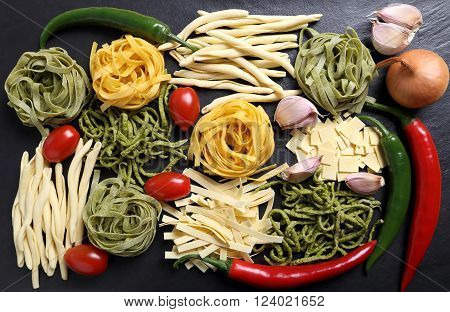 Different kinds of pasta on the black ceramic background.