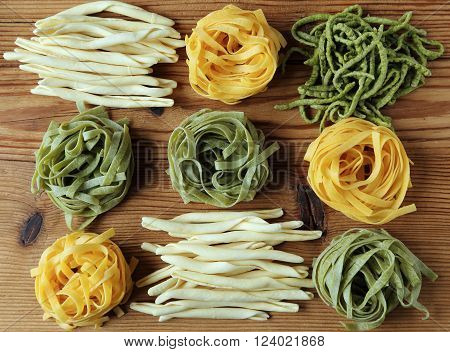 Different kinds of pasta on the wooden background.