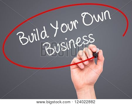Man Hand Writing Build Your Own Business With Black Marker On Visual Screen.