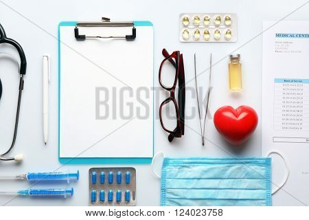 Doctor table with medicines, clipboard and glasses, top view
