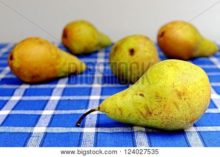 Five organic pears on a blue placemat with motive cube
