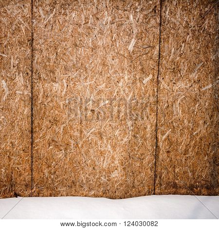 Old weathered plywood fence and a ground covered with snow