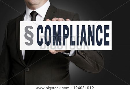 compliance placard is held by businessman background