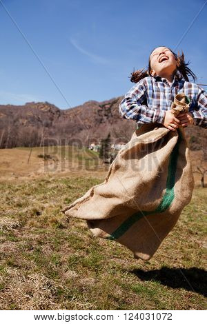 Little girl jumps in a sack of potatoes, she is happy