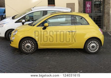 ROME ITALY - CIRCA OCTOBER 2015: Yellow Fiat 500 car (new version) parked in a street of the city centre