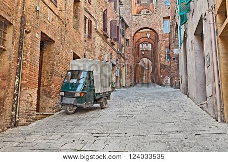 SIENA ITALY - MARCH 22: picturesque Italian alley in the old town with ancient dwellings, archs, and three-wheeled vehicle Ape Piaggio, on March 22, 2016 in Siena, Tuscany, Italy