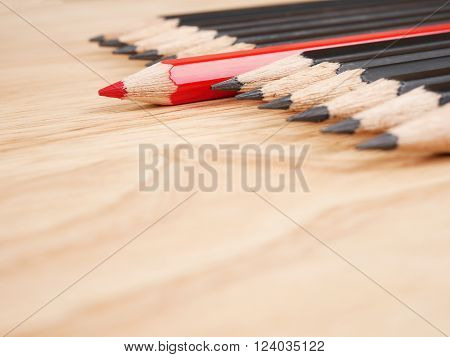 Red pencil standout from black pencil, leadership business concept