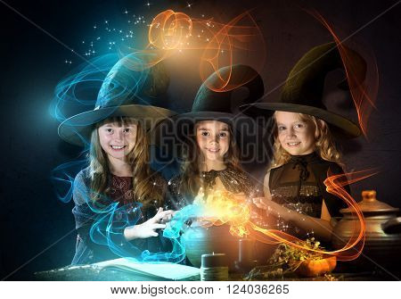 Three little Halloween witches reading conjure from magic book