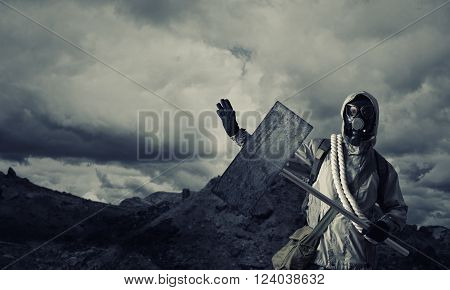 Stalker in gas mask with blank banner. Place for your text