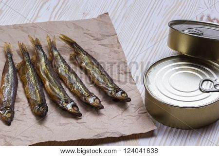 Smoked capelin and conserve tins on light wooden background