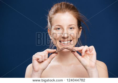 Smiling woman holding chocolate over blue background