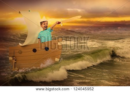 Portrait of a child with a wooden sword. He floats in a cardboard boat on the sea.