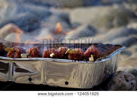 Foil barbeque with kebabs on a pebble beach