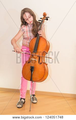 Pretty young girl practice playing cello standing on wall background