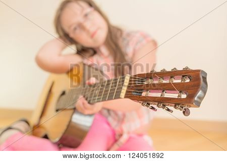 Girl sitting on floor with russian seven-string acoustic guitar