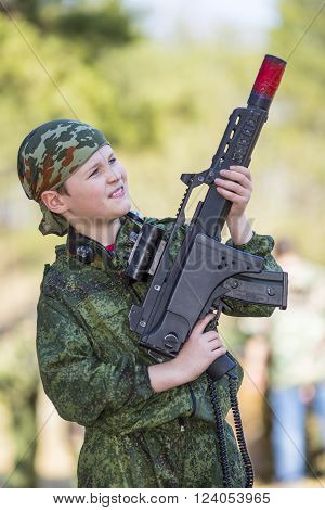 Teen boy with a gun in camouflage playing laser tag ** Note: Shallow depth of field
