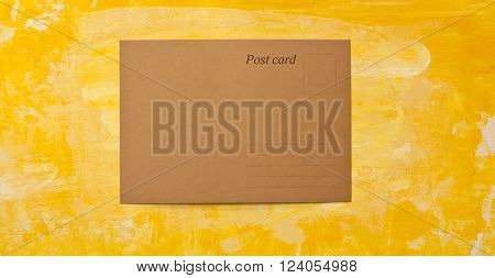 A brown paper postcard on a golden yellow abstract painterly background texture with a place for text