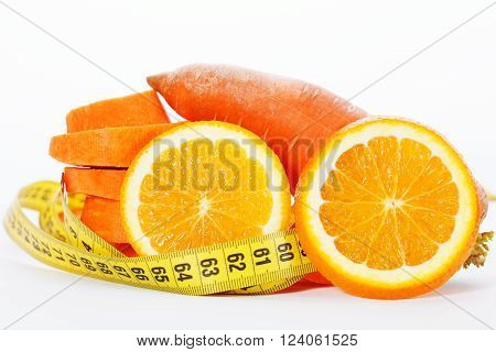Slices of orange with slices of carrot and measuring tape
