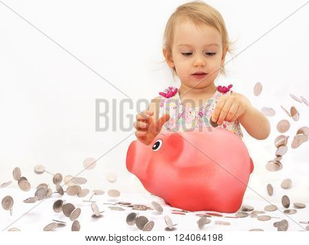 Two-year old girl throwing money into piggy bank.