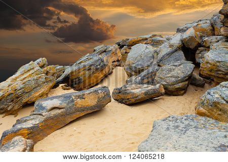 Stone desert. Old rocks on yellow sand on fantastic sunset background . Orange clouds illuminated by sun.