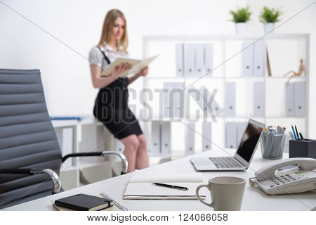 Office table, blurred blonde businesswoman standing at table at background. Office. Concept of work.