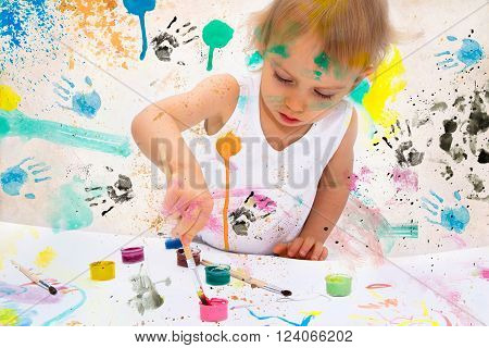 Two-year old girl paints with poster paintings.
