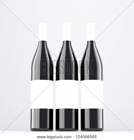 Three wine bottles aranged in line, blank labels on them. Dark glass. Concept of bottling wine. Mock up. 3D rendering.