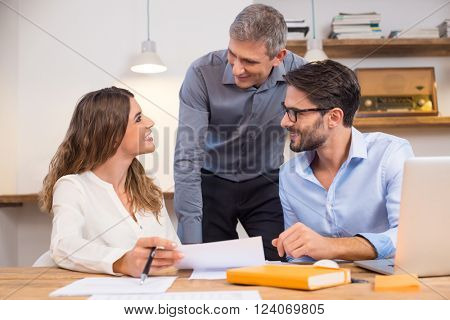 Senior manager interacting with new trainees in office. Young smiling employees in a conversation with executive in office. Happy business teamwork smiling in office with leader.