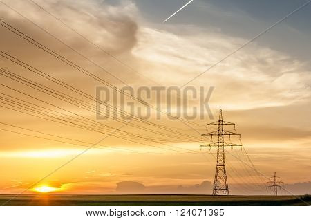 transmission line with poles in front of a yellow and amber sky at sunset or sunrise with condensation trail