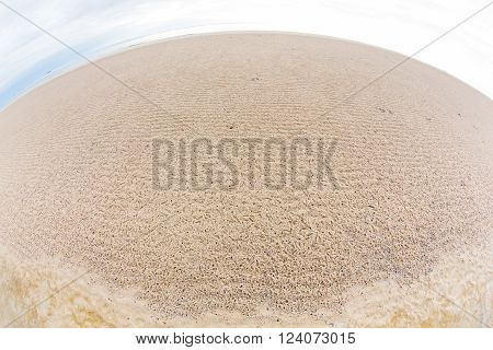 Abstract ghost crab hole on the beach shot with fisheye lens