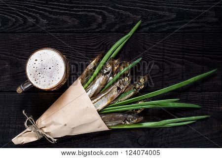 Smoked capelin with green onions in paper cornet and beer in a mug on dark wooden background. Top view