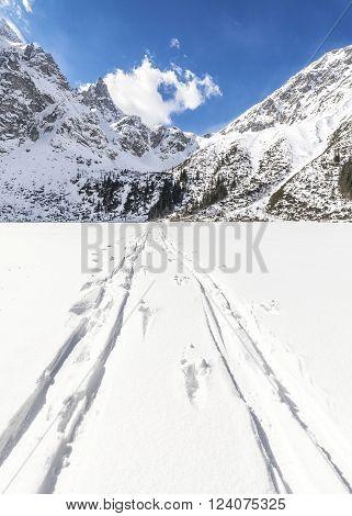 Cross-country skis traces on snow on frozen Lake Morskie Oko Polish Tatra Mountains.