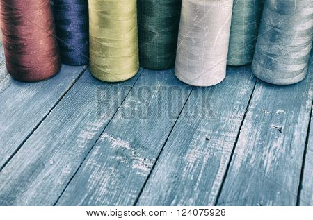 Vintage photo colored threads for sewing and embroidery on the wooden table