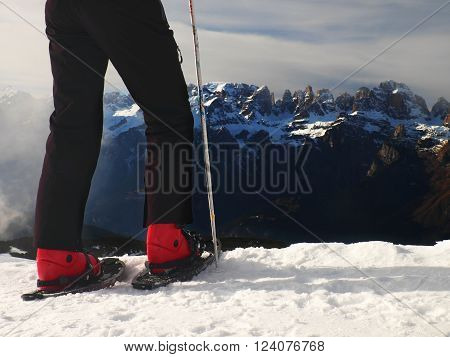 Hiker in red winter jacket with snowshoes in hands. Fogy winter day at peak