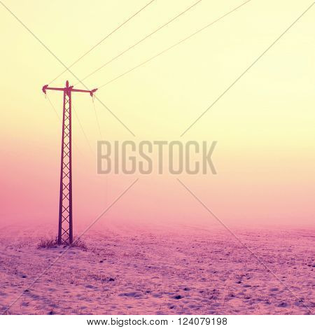 Chilly windy morning on the meadow. Old iron electric pole in countryside with the pink sky in background.