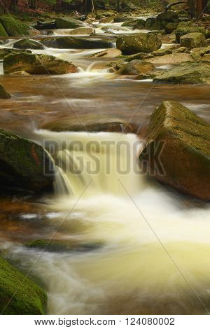 Rapid stream flowing down over stones. Blurred waves of Alpine brook running over boulders and stones, reflections in the water level.